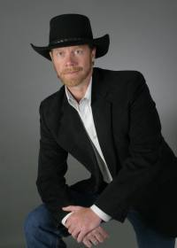 Guy Smith | leaning in black jacket and hat