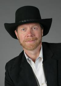 Guy Smith | head shot in black jacket and hat
